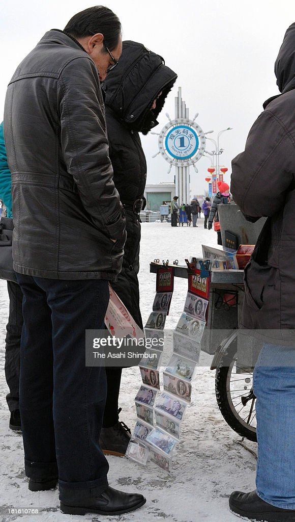 Chinese tourists look North Korean bank notes at a stall selling North Korea related souvenirs on February 12, 2013 in Dandong, China. North Korea confirmed it had successfully carried out an underground nuclear test as a shallow earthquake with a magnitude of 4.9 was detected by several international monitoring agencies. South Korea and Japan both assembled an emergency meeting of their respective national security teams after the incident.