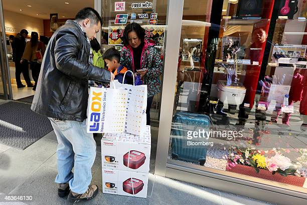 Chinese tourists organize their purchases outside a Laox Co store in the Ginza district of Tokyo Japan on Monday Feb 16 2015 Foreign visitors to...