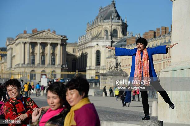 Chinese tourists pose for a picture with Versailles castle in the background on November 15 2015 in Paris France As France observes three days of...