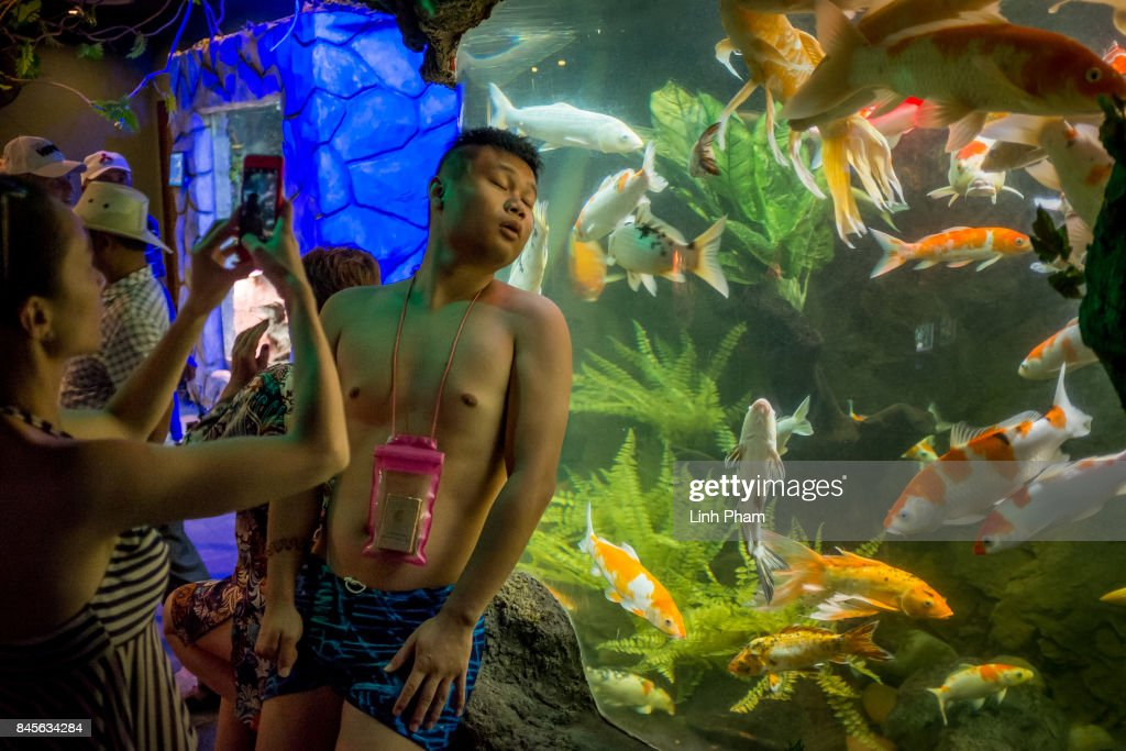 Chinese tourists pose for photos with fish in the aquarium at Vinpearl Land Amusement Park on September 8, 2017 in Nha Trang, Vietnam. With a total of 2.7 million tourists in 2016, China is Vietnam's largest source of visitors, as most mainland Chinese head to the coastal cities of Da Nang or Nha Trang located in the centre of the country and famed for their beaches, historical sights and seafood. Based on reports, Chinese tour groups have grown to 150 to 200 while the influx has caused problems such as the lack of Chinese speaking staff and inexperience in dealing with inappropriate behavior by the mainland Chinese who have been criticized for their lack of manners in public spaces, including spitting and urinating in public and being noisy at religious places and heritage sites. As Vietnamese travel agencies aim to improve service for Chinese tourists, local media have reported the illegal use of the Renminbi in local markets and Chinese agents and guides acting without proper authorization, leading to distortions in how Vietnam's history and culture have been presented.
