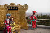 Chinese tourists posing for photographs wearing traditional clothing on a promenade above the Forbidden City Beijing China The Forbidden City was the...