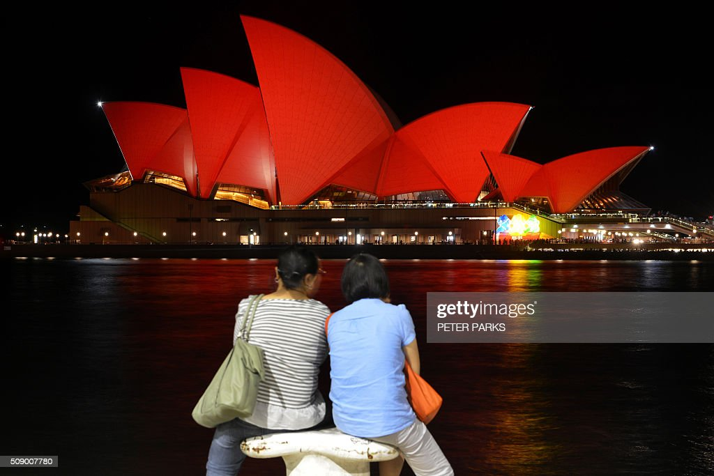 Chinese tourists sit and view the Sydney Opera House which is lit up red to welcome in the Lunar New Year in Sydney on February 8, 2016. The Lunar New Year of the Monkey begins on February 8. AFP PHOTO / Peter PARKS / AFP / PETER PARKS