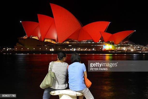 Chinese tourists sit and view the Sydney Opera House which is lit up red to welcome in the Lunar New Year in Sydney on February 8 2016 The Lunar New...