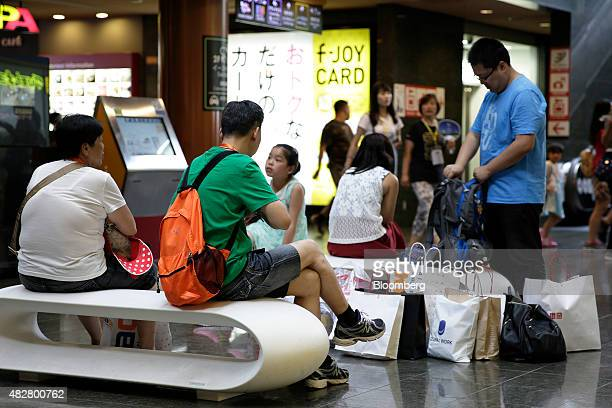 Chinese tourists sit with their shopping bags at the Canal City Hakata commercial complex in Fukuoka Japan on Friday July 24 2015 Four million...