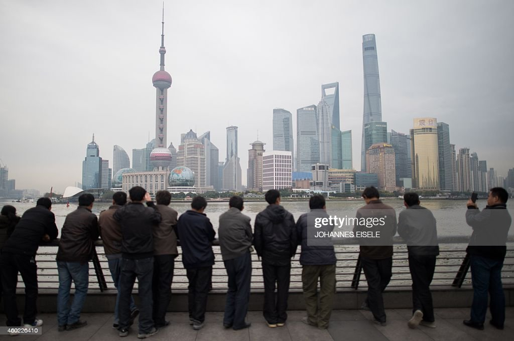 Chinese tourists stand along the promenade on the Bund overlooking the Huangpu River against the skyline of the Pudong district in Shanghai on...