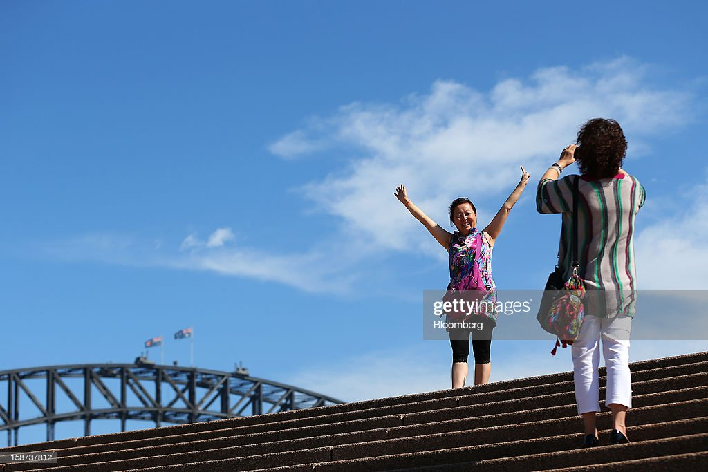 Chinese tourists take photographs in front of the Sydney Harbour Bridge in Sydney, Australia, on Monday, Dec. 24, 2012. At least 150,000 people from mainland China and across Asia are projected to descend on Sydney, Australia's most populous city, during the New Year's Eve and Chinese New Year period. Photographer: Brendon Thorne/Bloomberg via Getty Images