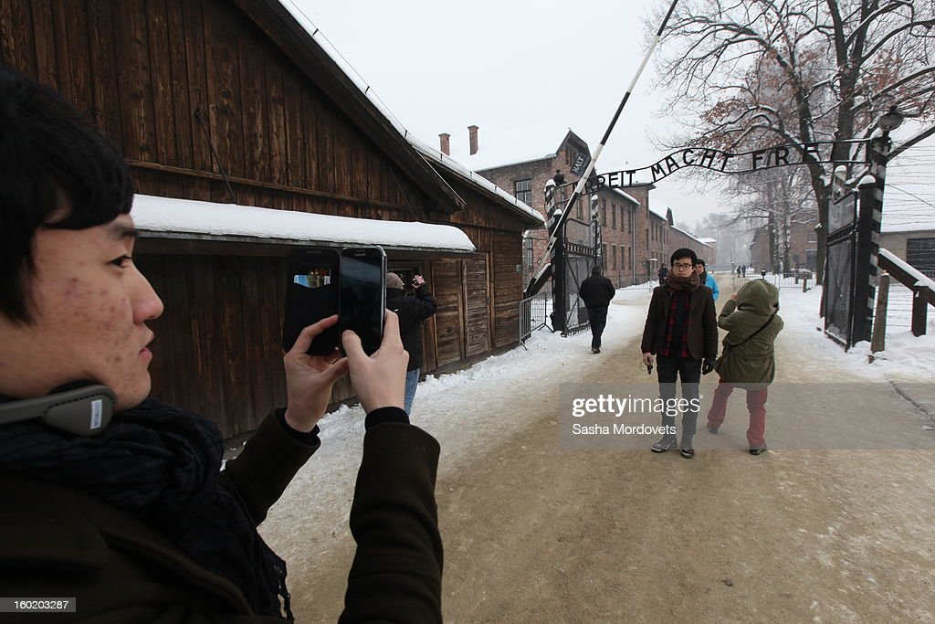 Chinese tourists take photos at the former Auschwitz Birkenau Nazi concentration camp January 27, 2013 near Oswiecim, Poland. A ceremony marked the 68th anniversary of the liberation of the camp during International Holocaust Remembrance Day.