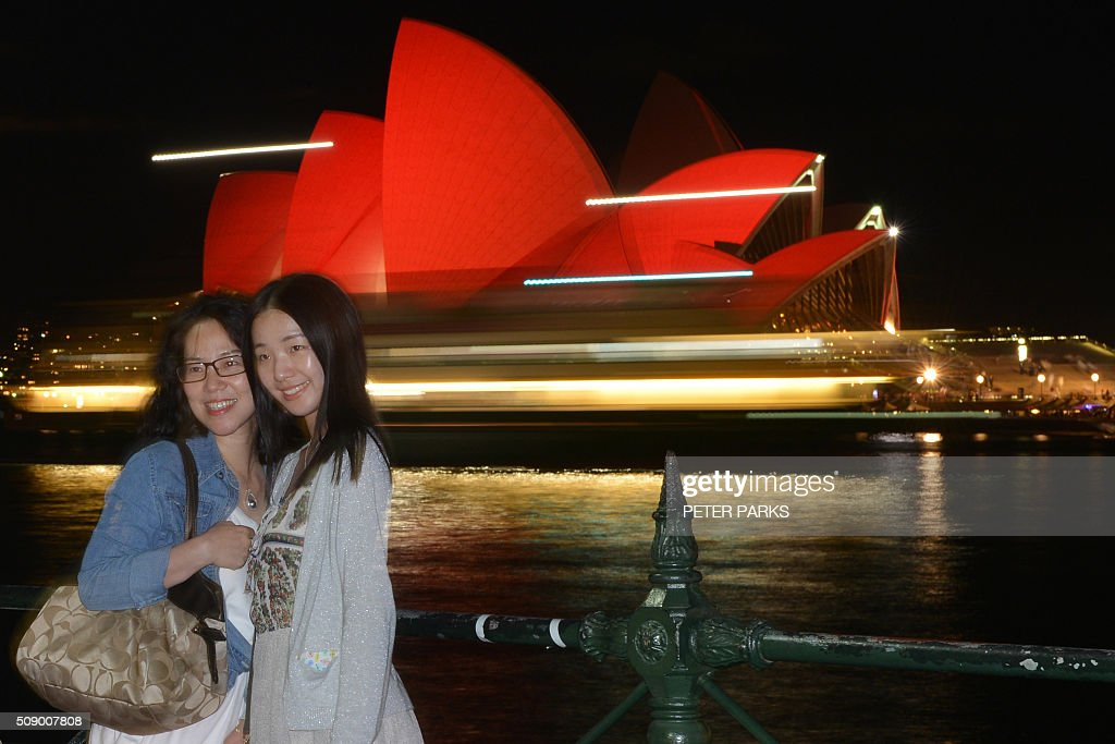 Chinese tourists take photos in front of the Sydney Opera House which is lit up red to welcome in the Lunar New Year in Sydney on February 8, 2016. The Lunar New Year of the Monkey begins on February 8. AFP PHOTO / Peter PARKS / AFP / PETER PARKS