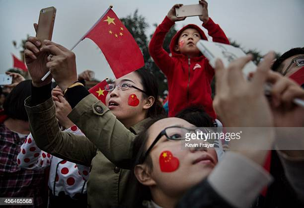 Chinese tourists take pictures near Tiananmen Square on the 65th National Day on October 1 2014 in Beijing China The day marks the founding of the...