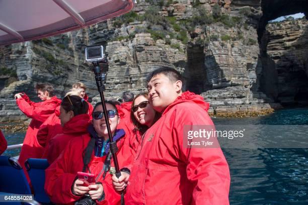 PENINSULA TASMANIA AUSTRALIA Chinese tourists taking selfies on Pennicott Wilderness Journey's cruise of the Tasman Peninsula's coastline in Tasmania...