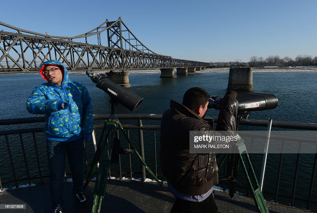 Chinese tourists view North Korea from the old the Sino-Korean Friendship bridge that was destroyed by the US Air Force in 1950 and used to link the North Korean town of Sinuiju with the Chinese town of Dandong on February 10, 2013. US Secretary of State John Kerry warned that North Korea's expected nuclear tests only increase the risk of conflict and would do nothing to help the country's stricken people. The country has vowed to carry out a third nuclear test soon, and concerns have been raised over the type of fissile material used in the device. AFP PHOTO/Mark RALSTON