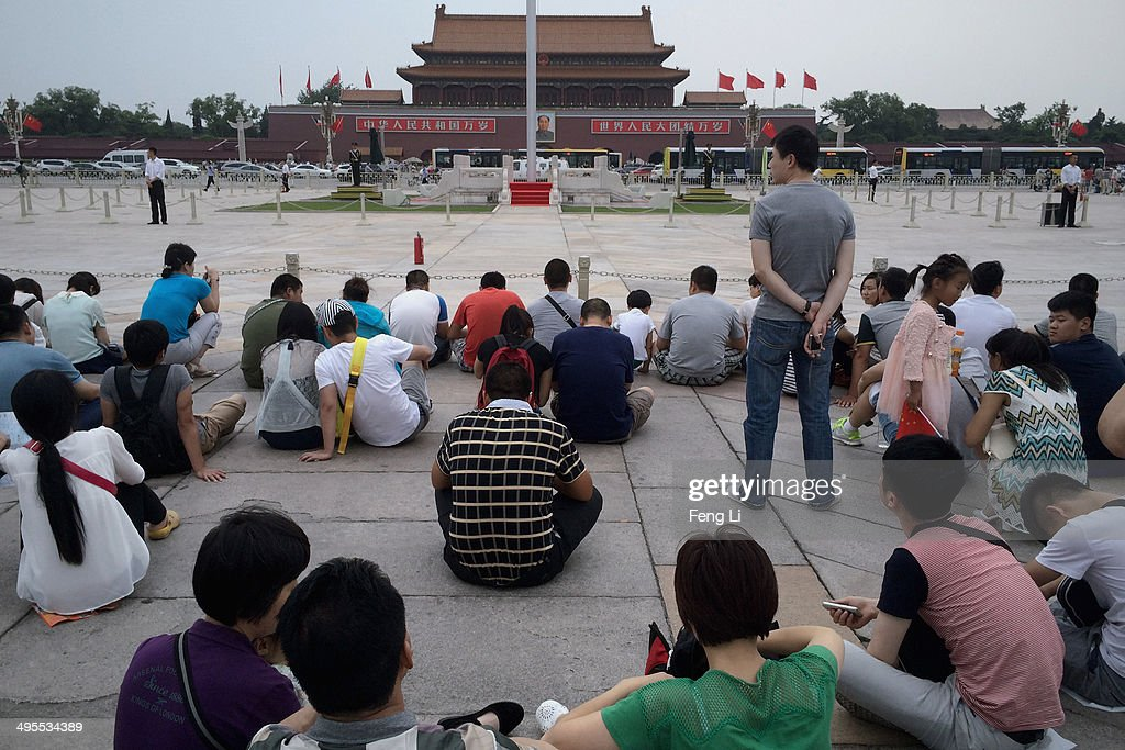 Chinese tourists wait for the customary ceremony of lowering flag in Tiananmen Square on June 4, 2014 in Beijing, China. Twenty-five years ago on June 4, 1989 Chinese troops cracked down on pro-democracy protesters and in the clashes that followed scores were killed and injured.