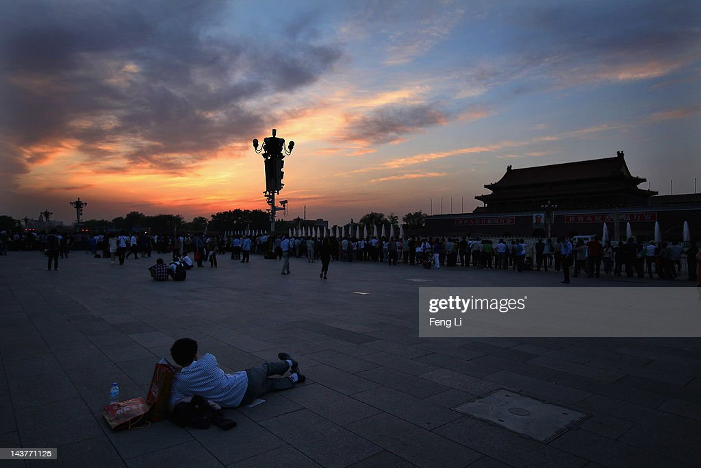 Chinese tourists wait for watching the customary ceremony of lowering flag at Tiananmen Square on May 3, 2012 in Beijing, China.