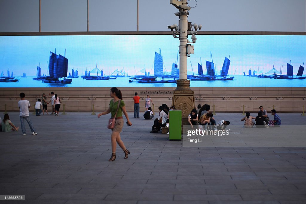 Chinese tourists wait for watching the customary ceremony of lowering flag under a LED screen at Tiananmen Square on June 3, 2012 in Beijing, China.