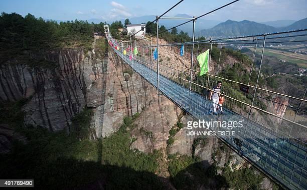 Chinese tourists walk across a glassbottomed suspension bridge in the Shiniuzhai mountains in Pingjiang county Hunan province some 150 kilometers...