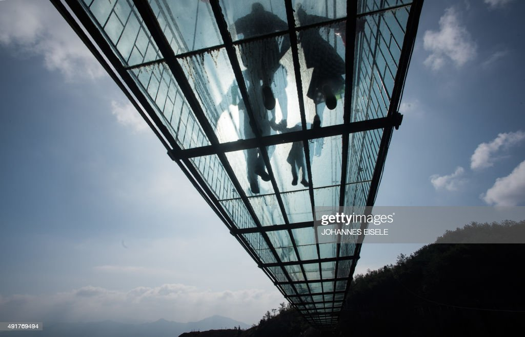 Chinese tourists walk across a glassbottomed suspension bridge in the Shiniuzhai mountains in Pingjiang county Hunan province some 150 kilometers...