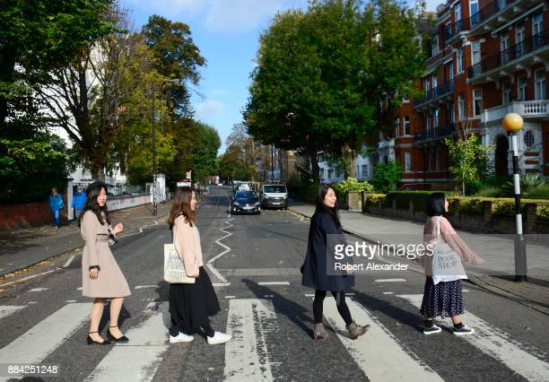 Chinese tourists walk across Abby Road in London England recreating the famous 1969 Beatles 'Abby Road' album cover photograph showing the four...