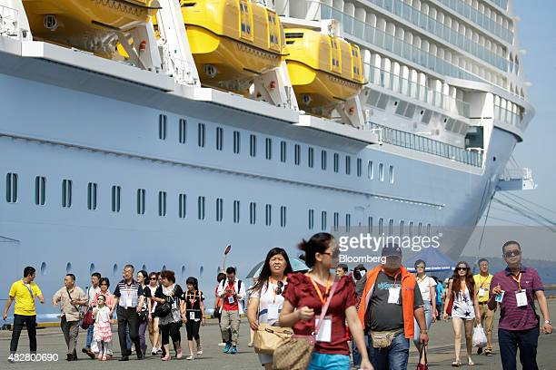 Chinese tourists walk along a pier after descending from the Quantum of the Seas cruise ship operated by Royal Caribbean Cruises Ltd's cruise line...