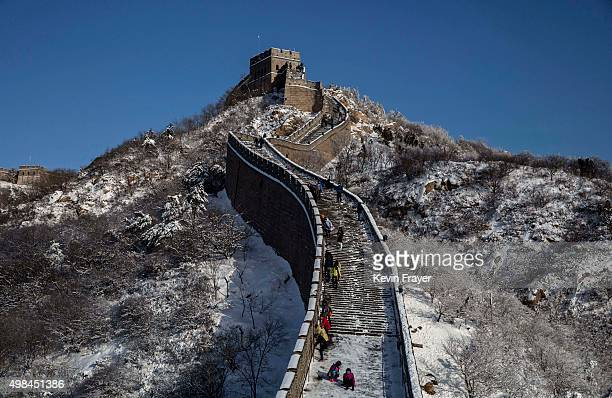 Chinese tourists walk on a slippery section of ice as snow is seen on the Great Wall after a snowfall on November 23 2015 near Beijing China China's...