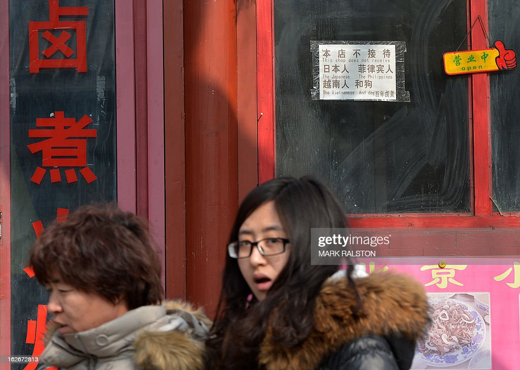 Chinese tourists walk past a sign that says 'This shop does not receive the Japanese, The Philippines, The Vietnamese and Dog' at the historic tourist district of Houhai in Beijing on February 26, 2013. China is currently in border disputes with Japan, Vietnam and the Philippines and has grown increasingly assertive in recent years in claiming islands and waters even without effective control of them -- in some cases hundreds of kilometres from the Chinese mainland and close to rival claimants' coasts. AFP PHOTO/Mark RALSTON