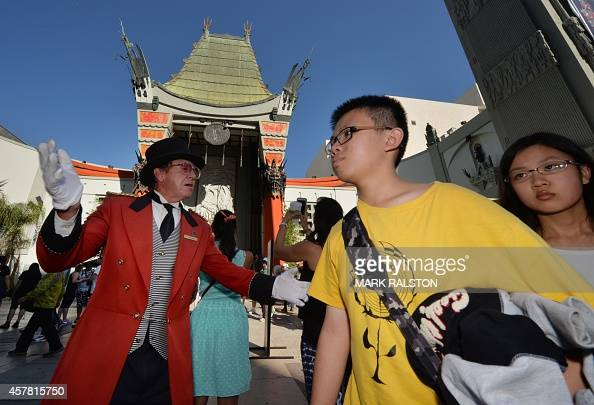 Chinese tourists walk past the TCL Chinese Theatre on Hollywood Boulevard in Hollywood California on October 24 2014 Local tourist officials say that...