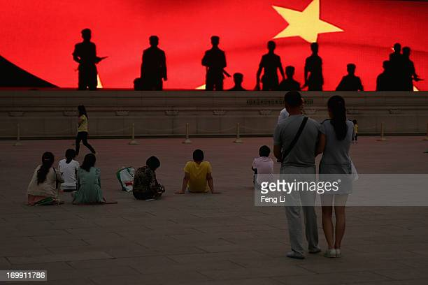 Chinese tourists watch a LED screen showing soldiers' shadow before the customary ceremony of lowering flag at Tiananmen Square on June 4 2013 in...