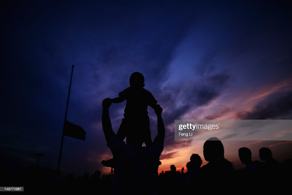 Chinese tourists watch the customary ceremony of lowering flag at Tiananmen Square on May 3, 2012 in Beijing, China.