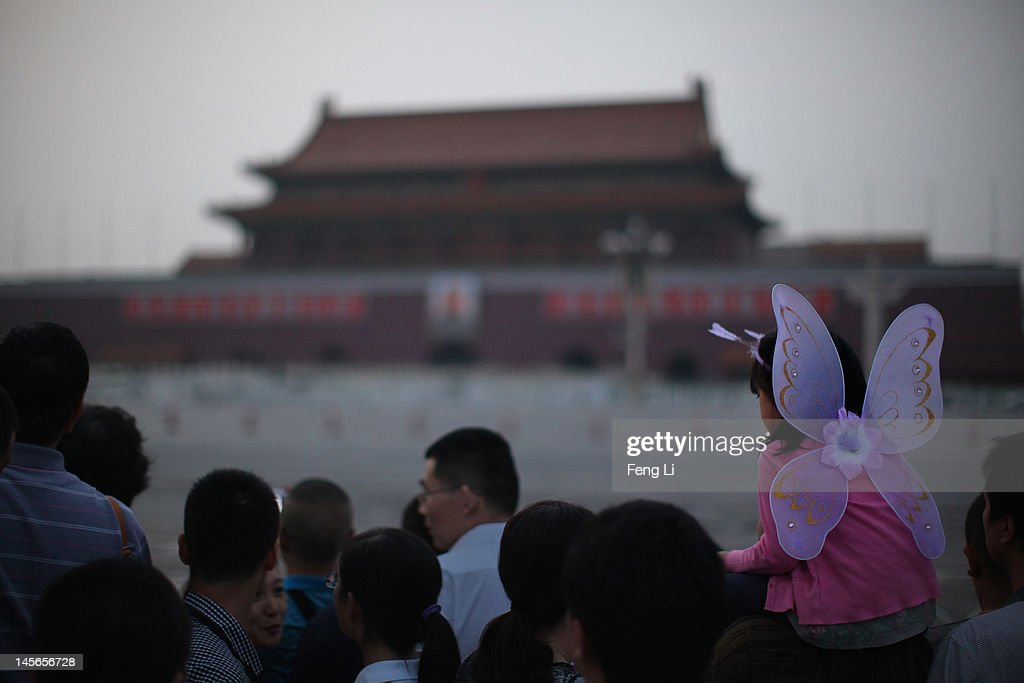 Chinese tourists watch the customary ceremony of lowering flag at Tiananmen Square on June 3, 2012 in Beijing, China.