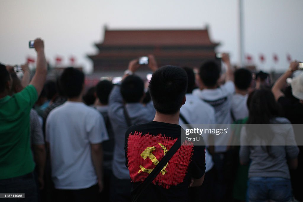Chinese tourists watch the customary ceremony of lowering flag at Tiananmen Square on June 4, 2012 in Beijing, China.