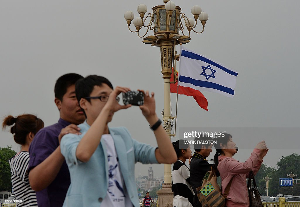 Chinese tourists watch the motorcade of Israeli Prime Minister Benjamin Netanyahu as he arrives to meet the Chinese President Xi Jinping at the Great Hall of the People in Beijing on May 9, 2013. Netanyahu is on a five day visit to China and will meet with Chinese President Xi Jinping and other top officials. AFP PHOTO/Mark RALSTON