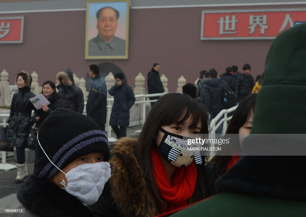 Chinese tourists wear face masks as they visit Tiananmen Gate and the portrait of Mao Zedong during heavy air pollution in Beijing on January 30, 2013. Beijing urged residents to stay indoors on January 30 as emergency measures were rolled out aimed at countering a heavy cloud of smog blanketing the Chinese capital and swathes of the country. AFP PHOTO/Mark RALSTON