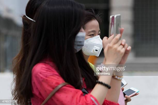 Chinese tourists wearing face masks take photographs with smartphones at the Ewha Womans University in Seoul South Korea on Monday June 8 2015 South...