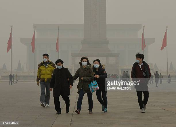 Chinese tourists wearing face masks visit Tiananmen Square as heavy air pollution continues to shroud Beijing on February 26 2014 Beijing's official...