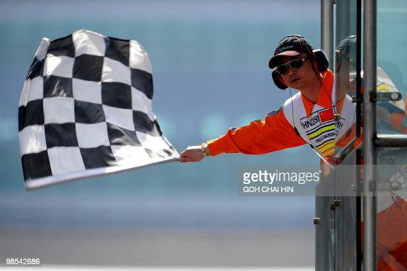 A Chinese track marshall waves the chequered flag to signal the end of the second qualifying session for Formula One's Chinese Grand Prix in Shanghai...