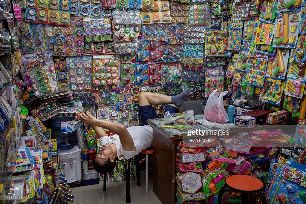 Chinese trader looks at his phone as he waits for customers at his stall selling wholesale plastic items at the Yiwu International Trade City on...