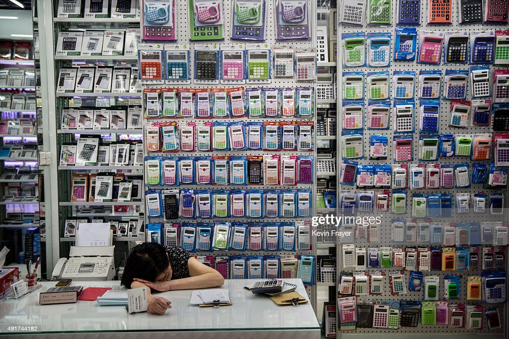 Chinese trader naps as she waits for customers at her stall selling wholesale calculators at the Yiwu International Trade City on September 19 2015...