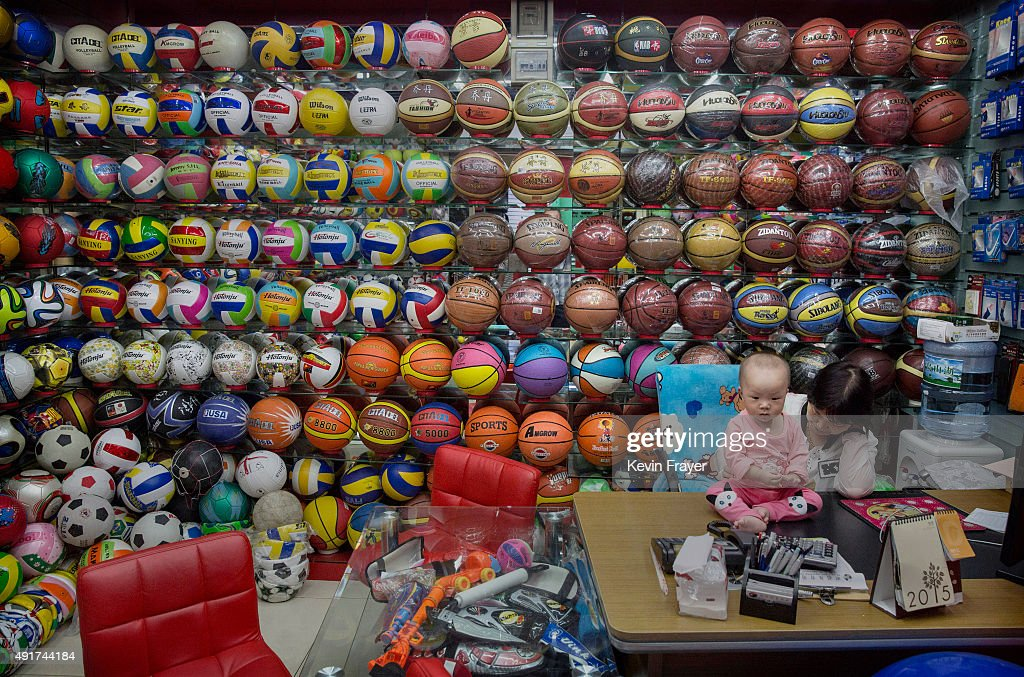 Chinese trader plays with her child as she waits for customers at her stall selling wholesale sports balls at the Yiwu International Trade City on...