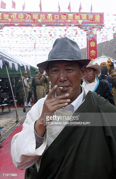 Chinese trader smokes a cigarette as he walks on Indian territory after crossing the ChinaIndia border at the 15000feet Nathu La Pass in India's...
