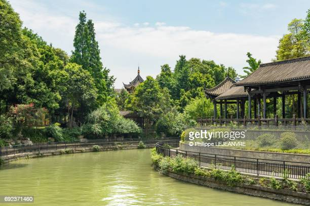 Chinese traditional building in vegetation with a canal in the f