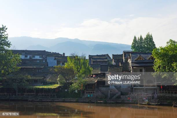 Chinese traditional houses by the river in the mountains