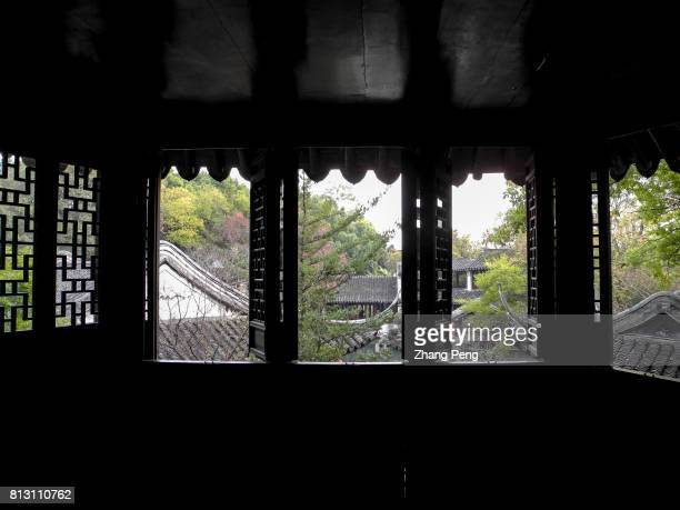 Chinese traditional tiled roofs seen from wooden carved windows on an attic The Retreat Reflection Garden built in Qing Dynasty is a notable...