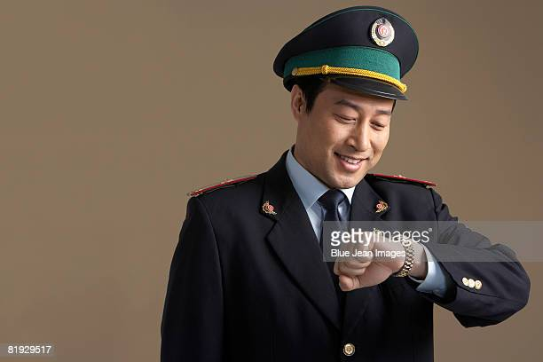Chinese train conductor looking at watch