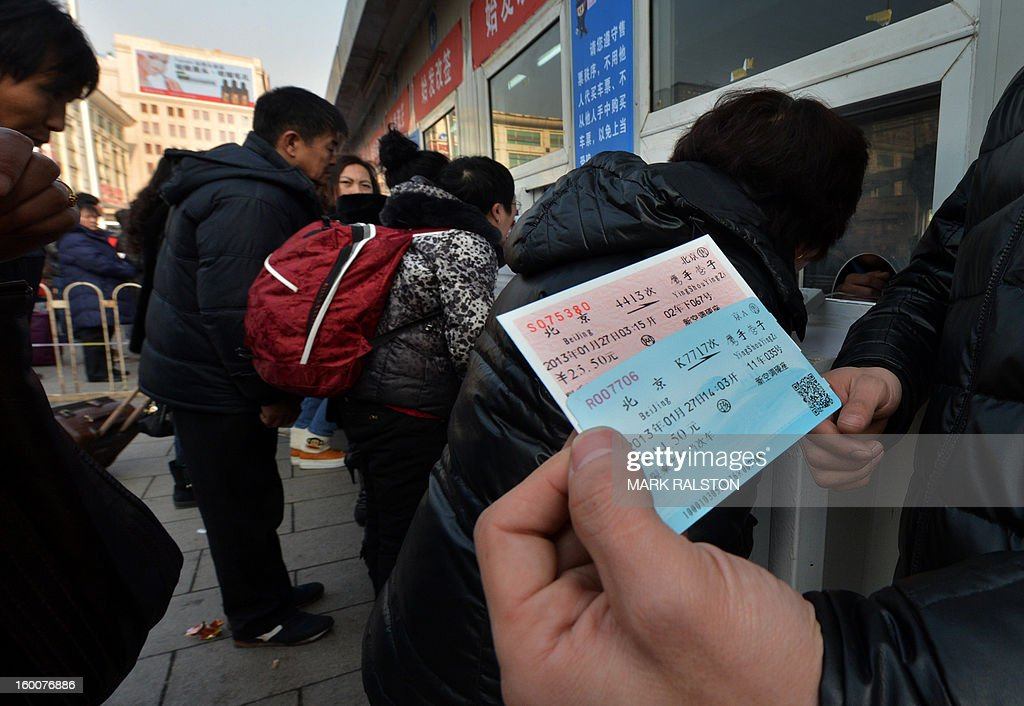 A Chinese traveller shows his ticket after collecting it from the ticket office as the annual Lunar New Year exodus begins at Beijing train station on January 26, 2013. The holiday also known as the Spring Festival sees tens of millions of migrant workers who provide the labour in the country's prosperous cities return to their villages and towns to spend time with the famillies left behind. AFP PHOTO/Mark RALSTON