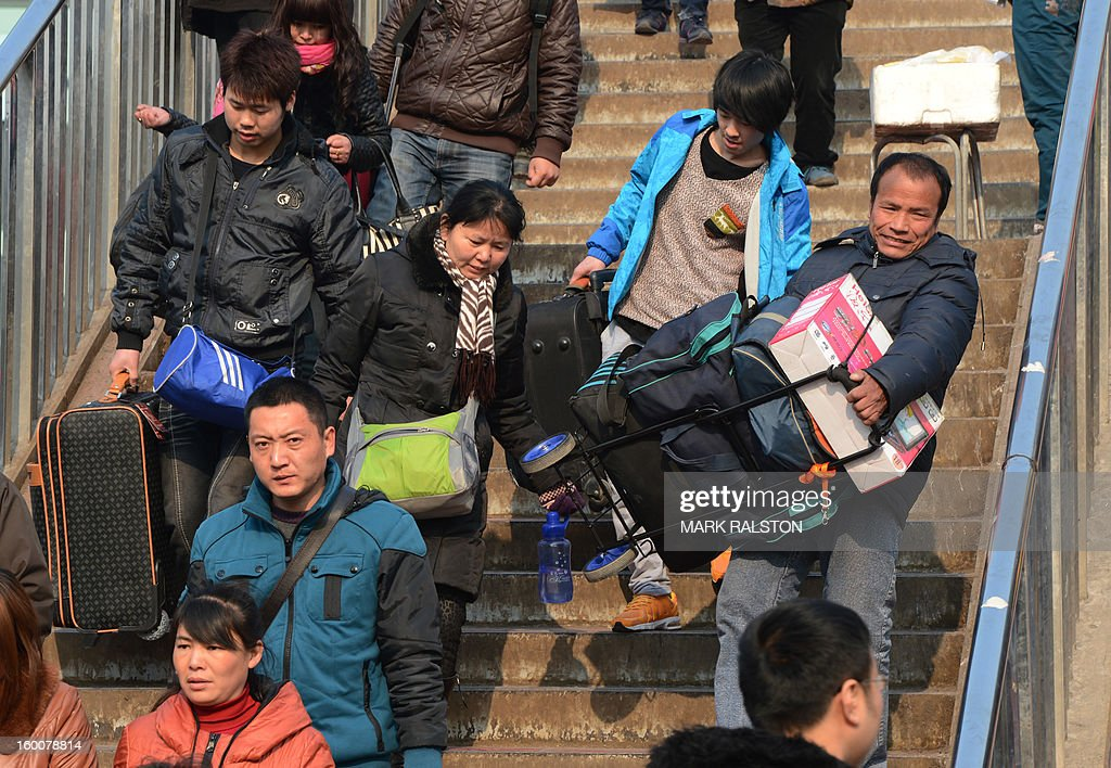 Chinese travellers arrive to board trains as the annual Lunar New Year exodus begins at Beijing train station on January 26, 2013. The holiday also known as the Spring Festival sees tens of millions of migrant workers who provide the labour in the country's prosperous cities return to their villages and towns to spend time with the famillies left behind. AFP PHOTO/Mark RALSTON
