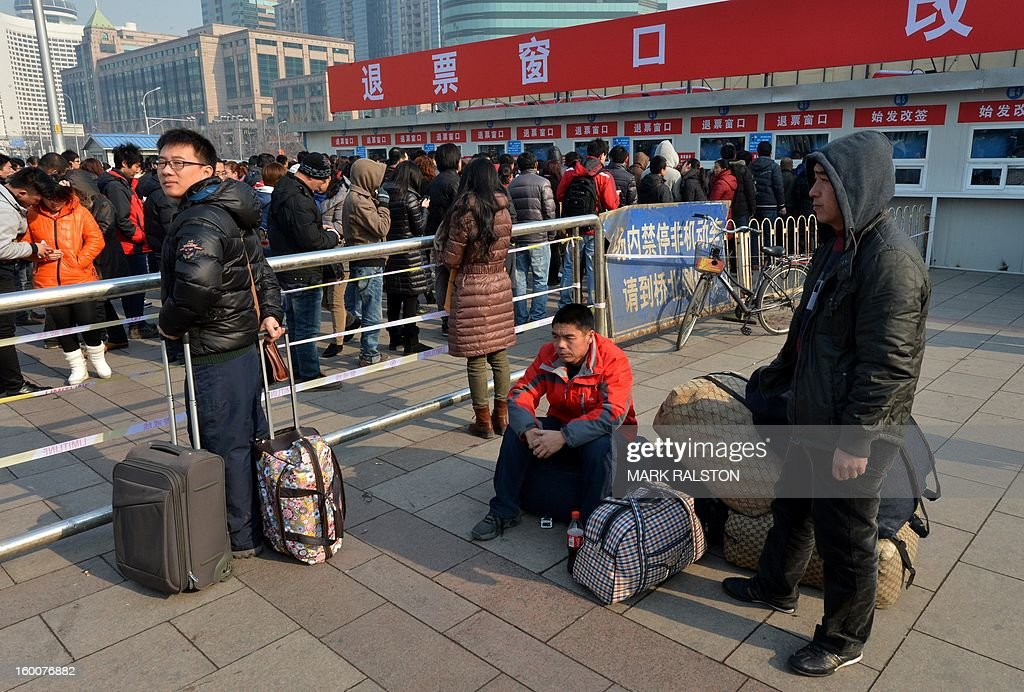 Chinese travellers wait to buy tickets as the annual Lunar New Year exodus begins at Beijing train station on January 26, 2013. The holiday also known as the Spring Festival sees tens of millions of migrant workers who provide the labour in the country's prosperous cities return to their villages and towns to spend time with the famillies left behind. AFP PHOTO/Mark RALSTON