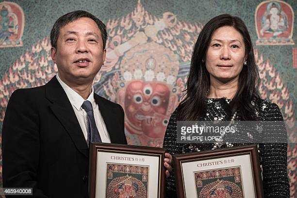 Chinese tycoon Liu Yiqian and his wife Wang Wei hold framed pictures reproducing a 600yearold Tibetan embroidered artwork called thangka at...