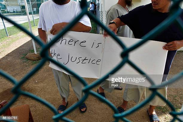 Chinese Uighur Guantanamo detainees show a homemade note of protest to visiting members of the media at Camp Iguana detention facility June 1 2009 at...