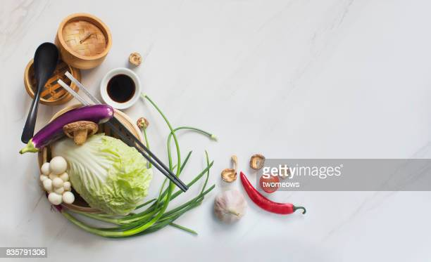 Chinese uncooked vegan food and eating utensils on marble table top.