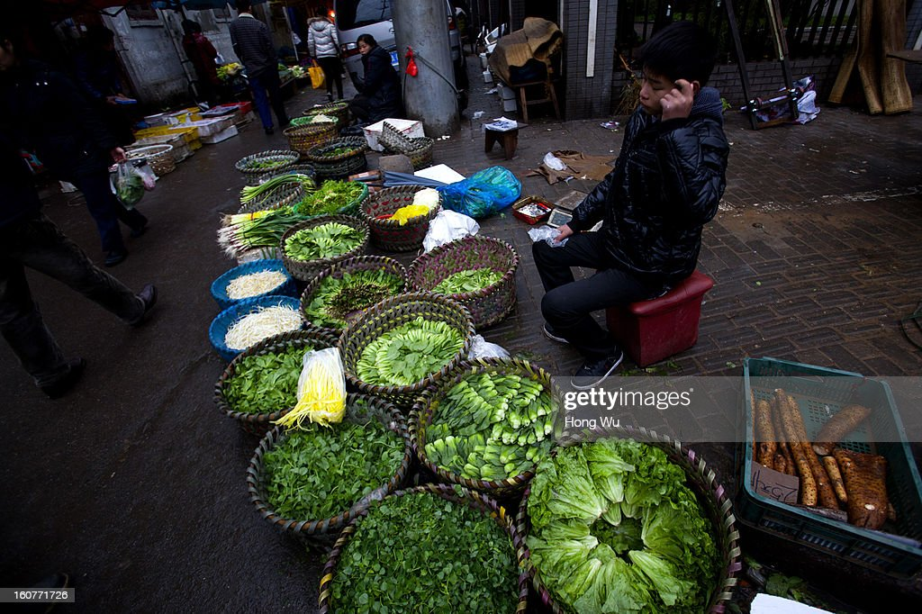 A Chinese vegetable vendor waits for customers at an outdoor market on February 5, 2013 in Shanghai, China. Chinese citizens are stocking up on food ahead of the upcoming Chinese Lunar New Year, also known as Spring Festival, is one of the most important festivals in China and falls this year on February 10, 2013.