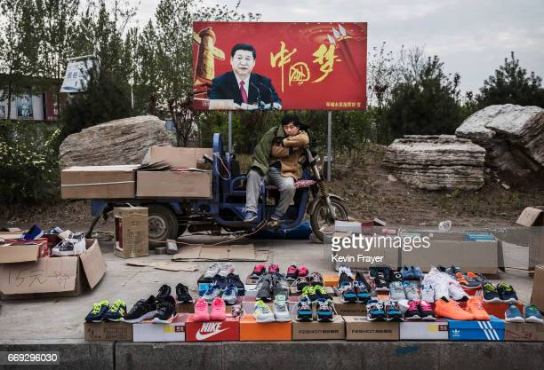 Chinese vendor sells sneakers and shoes in the street in front of a sign showing Chinese President Xi Jinping with 'China Dream' written on it on...